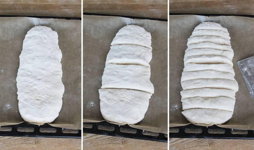 2. Dela degen i två delar. Låt den ena degen vila i kylen. Forma en längd av den andra biten med mjölade händer. Lägg den på en plåt med bakplåtspapper. Strö över mjöl och platta till den. Skär degen i ca 12 skivor med en degskrapa eller kniv.