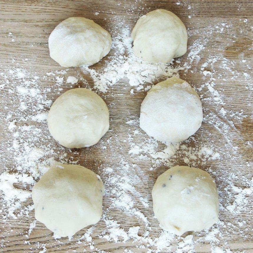 3. Knåda igenom degen på ett mjölat bakbord och dela den i ca 30 bitar. Forma släta bullar.
