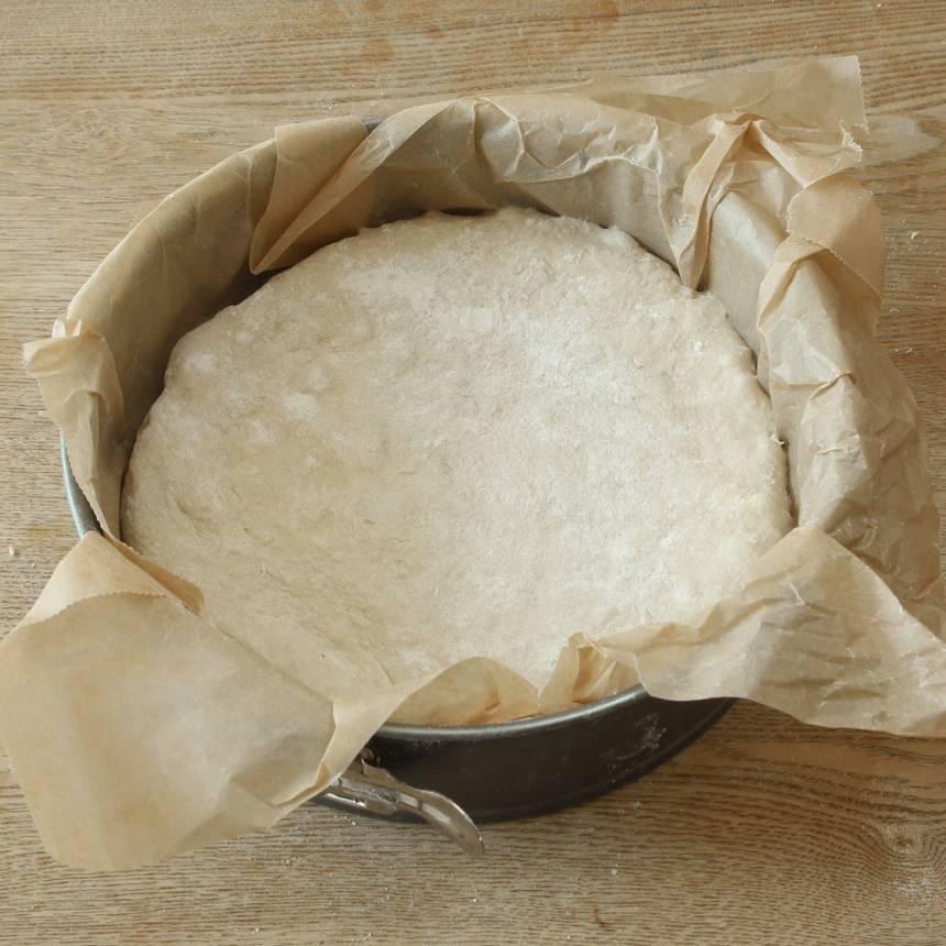 2. Tryck ut degen till en rund kaka i en form, ca 24 cm i diameter klädd med bakplåtspapper. Dela degen i 6–8 bitar med en degskrapa eller kniv. Täck formen med folié och ställ den i kylskåpet över natten.