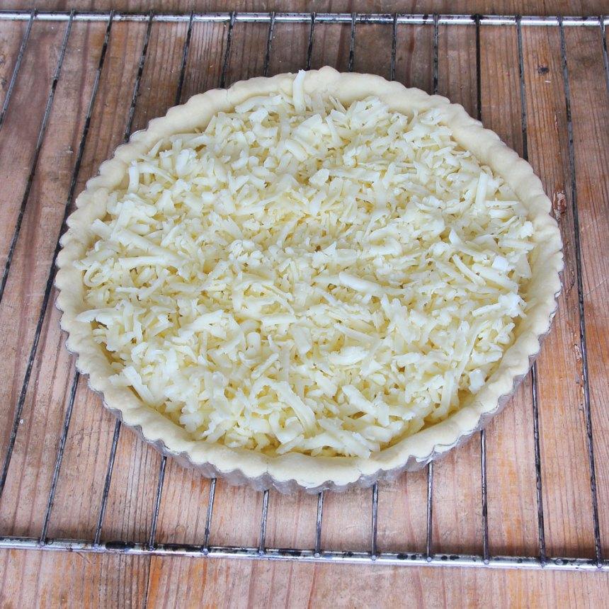 5. Strö osten över pajbottnen.