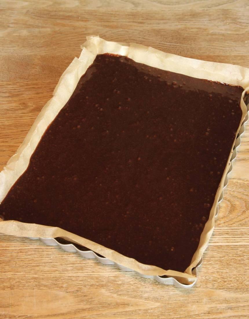 2. Lägg i ett bakplåtspapper i en form, ca 18 x 25 cm eller smörj och bröa den. Häll smeten i formen och bred ut den med en slickepott. (Det går också att göra kakan i en rund form, 23–24 cm i diameter). Grädda kakan mitt i ugnen i 23–26 min. Låt den svalna i formen.