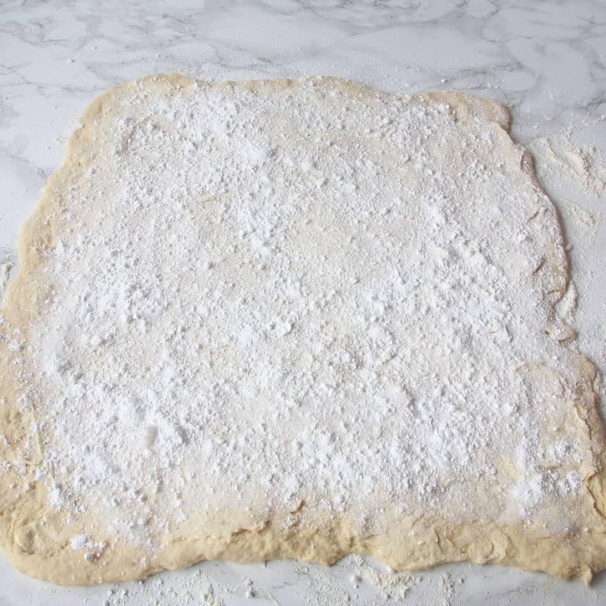 3. Bred ut hälften av smöret på degplattan och strö över hälften av vaniljsockret och florsockret.