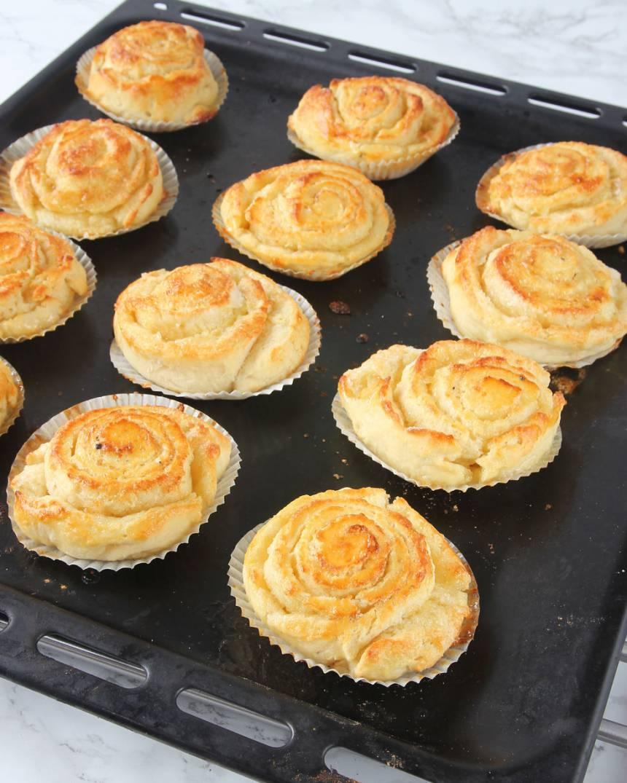 8. Grädda bullarna mitt i ugnen i 7–9 minuter. Låt dem kallna under bakduk på ett galler. Pudra över florsocker före servering.