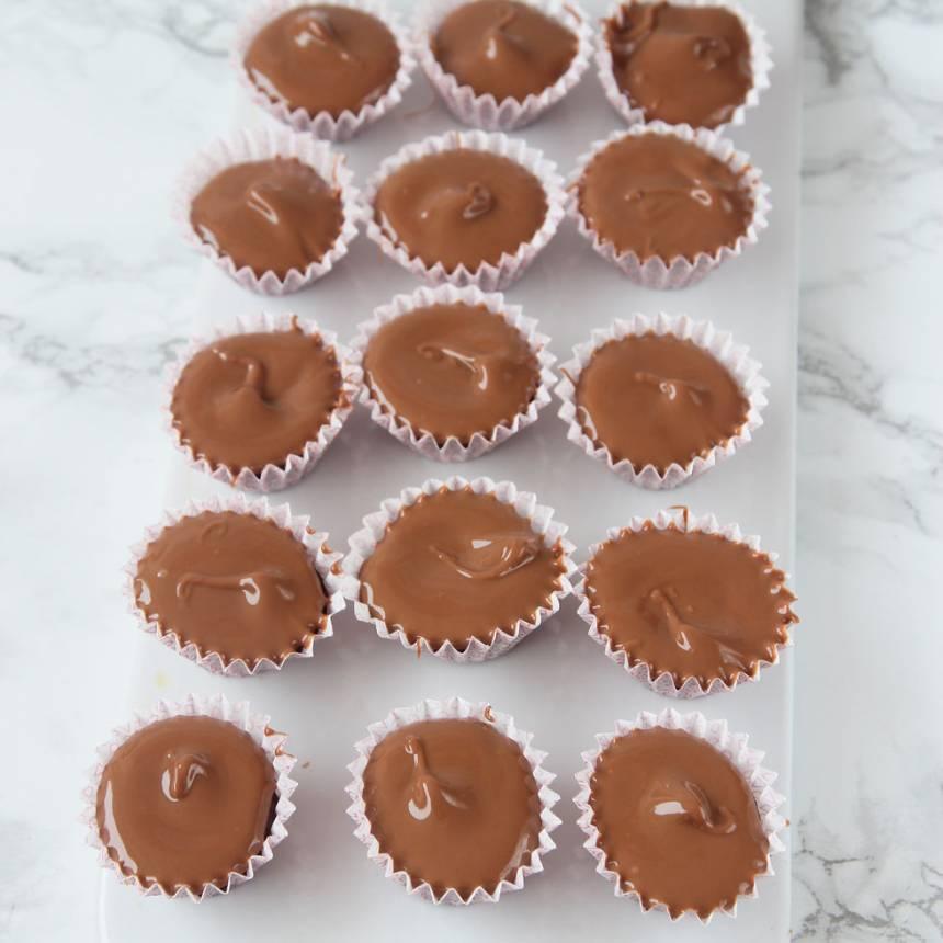 5. Smält mjölkchokladen (eller nougat) över vattenbad och lägg en klick som smälter ut ovanpå kolasmeten. Låt det stelna i frysen i några minuter.