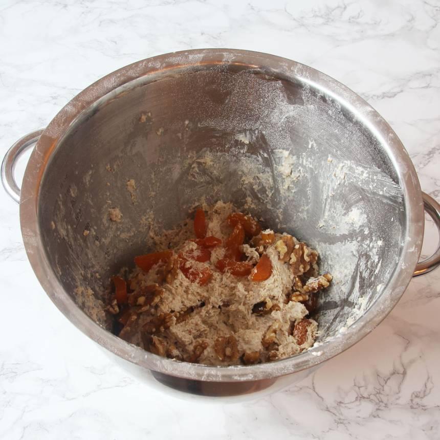 3. Rör ner aprikoser och valnötter i brödsmeten.
