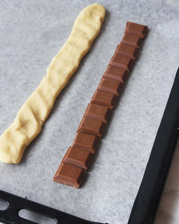 3. Lägg ut tre rader med mjölkchokladbitar, ca 25 cm långa, på en plåt med bakplåtspapper.