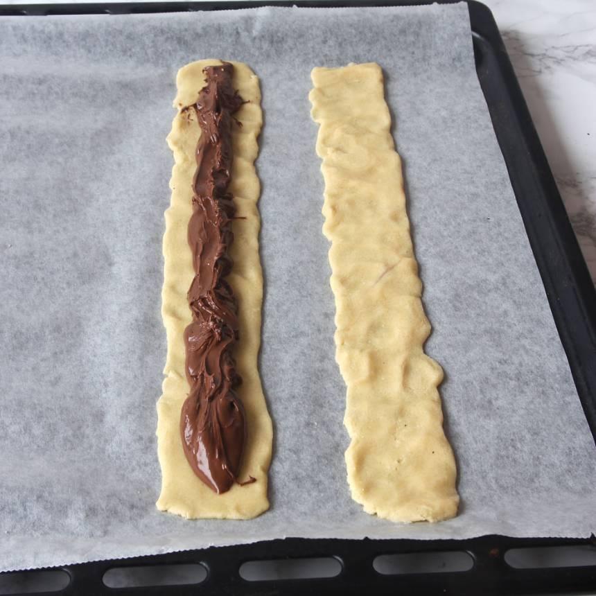 2. Rulla ut degen till fyra rullar, ca 25 cm långa, på en plåt med bakplåtspapper. Platta till dem. Ringla Nutella i mitten på två av längderna. Lägg på de andra längderna som lock. Tryck ihop kanterna.