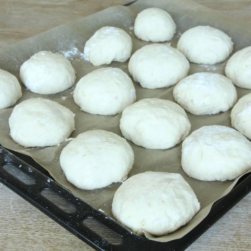 3. Dela degen i ca 20 bitar och forma dem till runda bollar. Lägg bröden på en plåt med bakplåtspapper och låt dem jäsa i 30 min. Sätt ugnen på 250 grader.