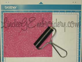 LindeeGEmbroidery-Use brayer to smooth fabric to mat