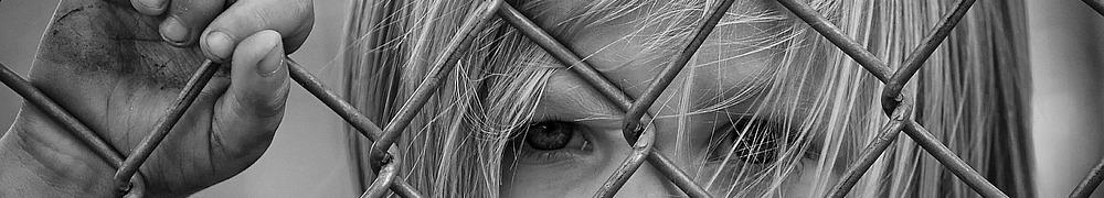 Kind hinter Zaun