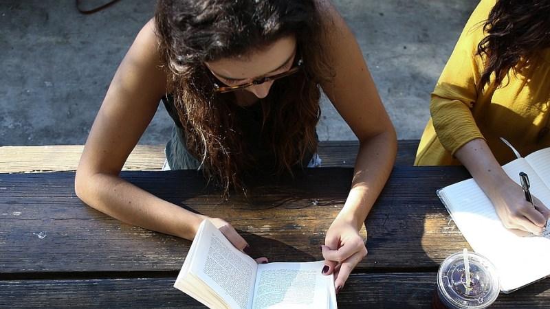 Zwei junge Frauen sitzen an einem Tisch und lernen gemeinsam