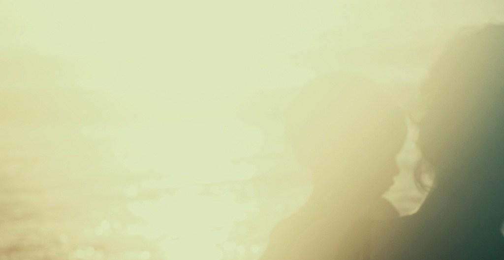 Mutter mit Kleinkind im Arm, am Strand im Gegenlicht