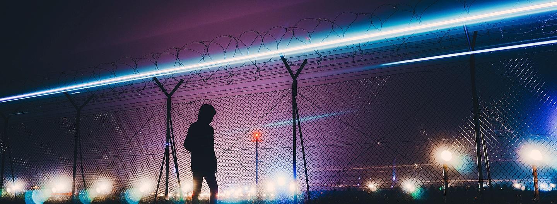 Flüchtling am Zaun bei Nacht