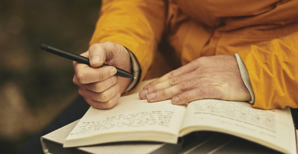 Erwachsener lernt und macht Notizen in seinem Arbeitsbuch