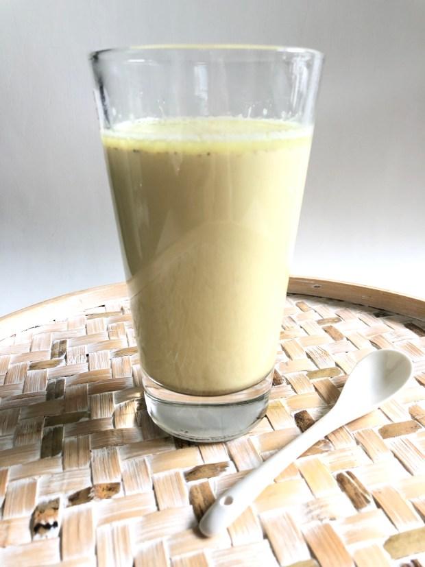 Ein Glas Goldene Milch auf einem Bambus-Tablett