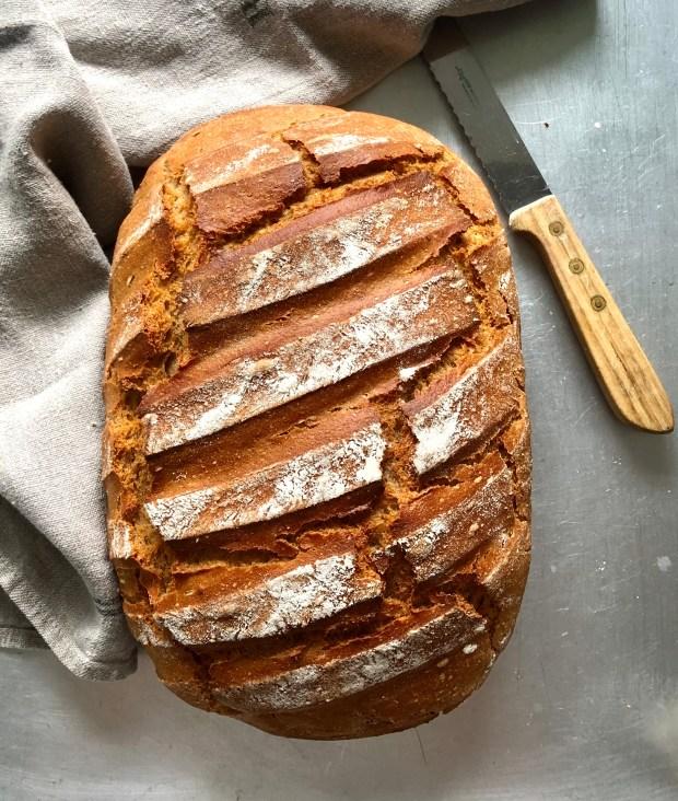 Ein Laib Buttermilch-Brot mit Brotmesser und Tuch auf Alu-Platte
