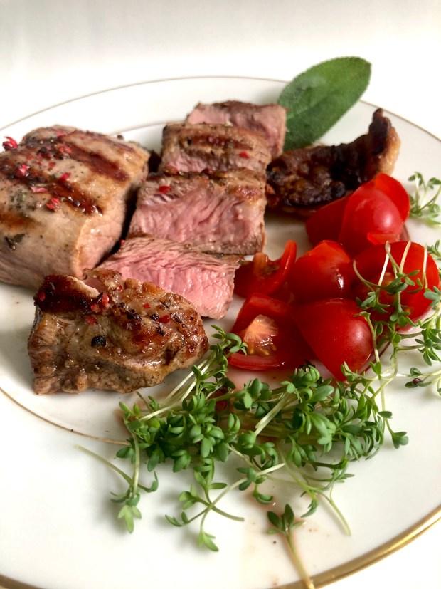 Gebratene Kalbssteaks  auf weißenm Teller  mit Kresse, Tomate und Salbei