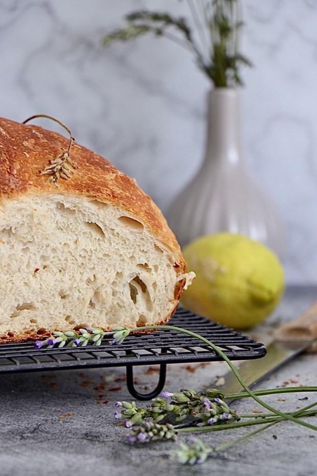 Ein Anschnitt vom Lavendel-Zitronen-Brot auf einem Abkühlgitter mit Zitrone und Lavendel dekoriert.