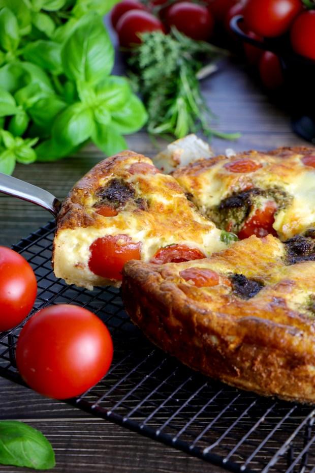 Tomaten-Tarte Caprese angeschnittener einem Stück auf Tortenheber  auf    Abkühlgitter mit Tomaten