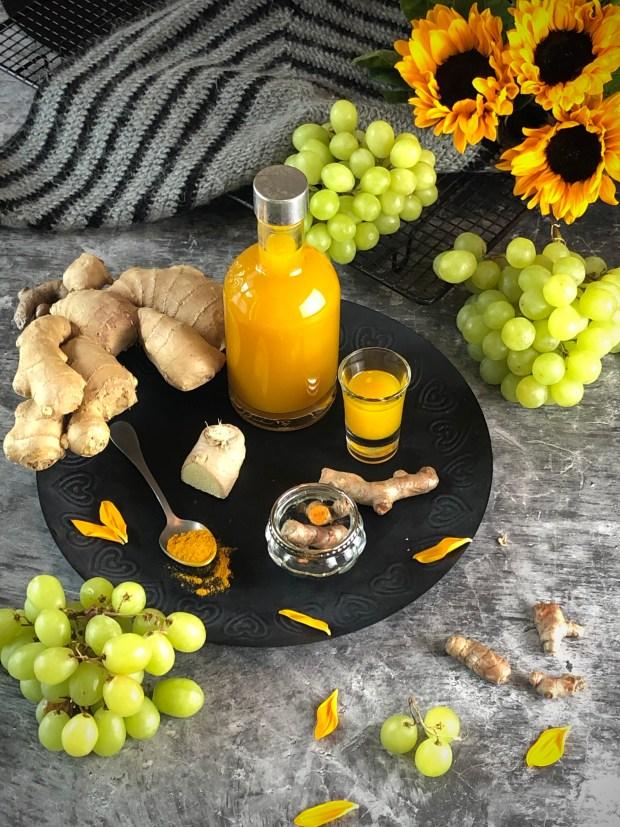 Eine Flasche Kurkuma-Ingwer-Trauben-Sirup auf einem Tablett mit Kurkuma  und Ingwer    Daneben Weintrauben und Sonnenblumen