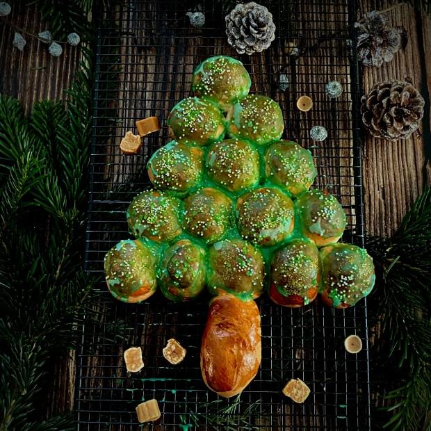 Hefe-Tannenbaum mit grünem Zuckerguss auf schwarzem Abkühlgitter mit Karamell-Dekor