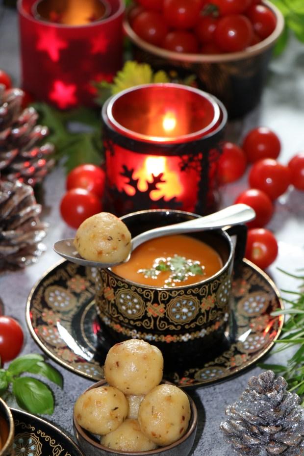 Festliche Tomaten-Suppe in schwarzem Geschirr angerichtet. Klösschen in einer extra Schüssel. Weihnachtlich dekoriert