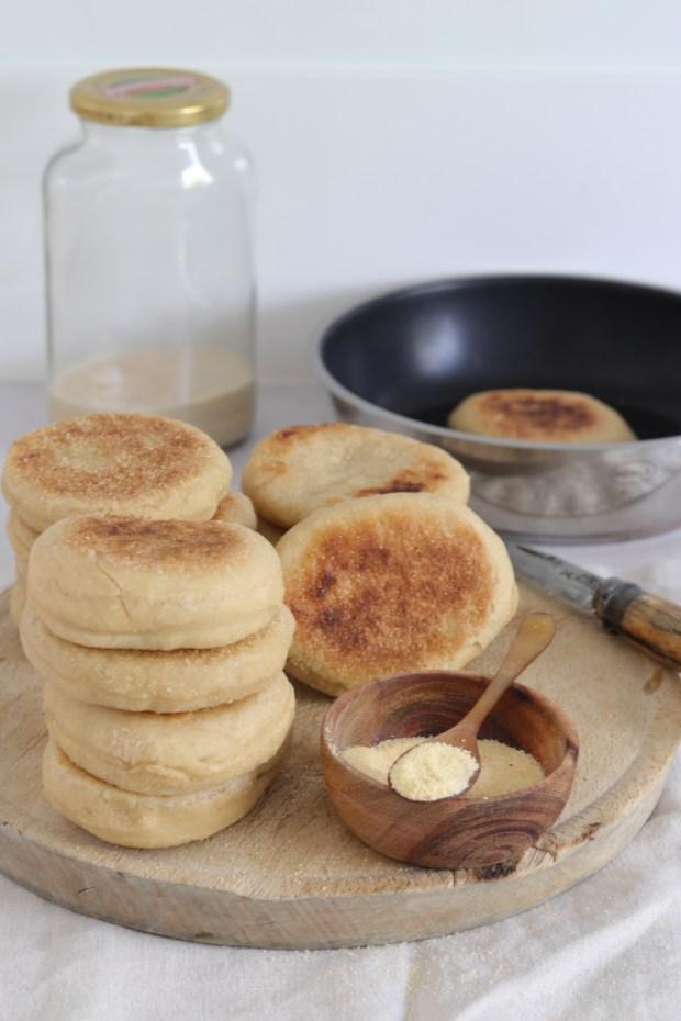 Gebackene English-Muffins auf rustikalem Holzbrett gestapelt