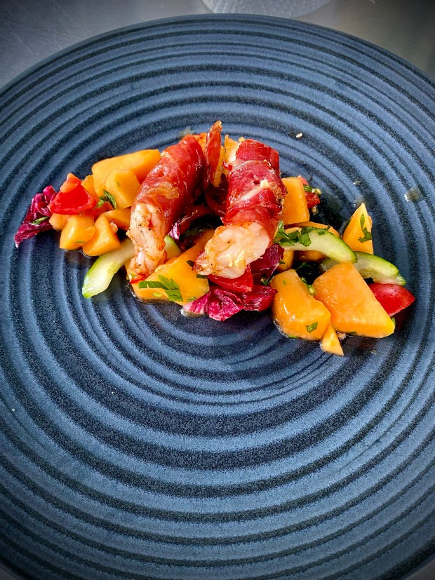 Zwei Serrano-Garnelen auf Melonen-Salat auf dunklem Teller angerichtet