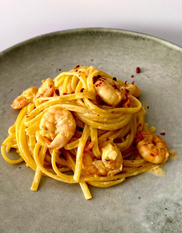 Schnelle Safran-Pasta mit Garnelen auf grauem Teller angerichtet