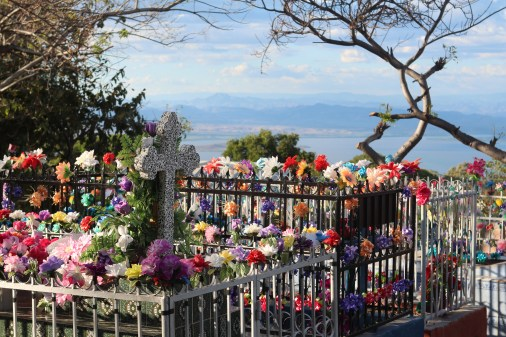 A colorful mountainside cemetery covered in silk flowers.