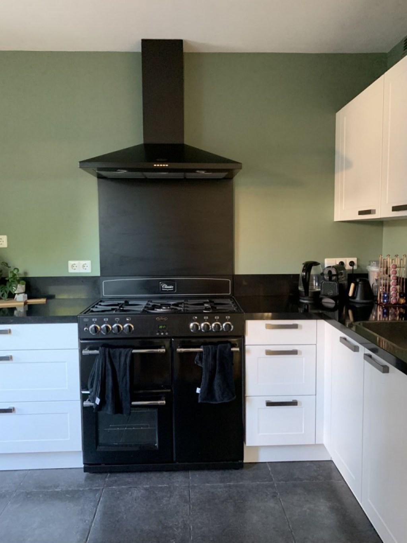 Een witte keuken met zwart fornuis