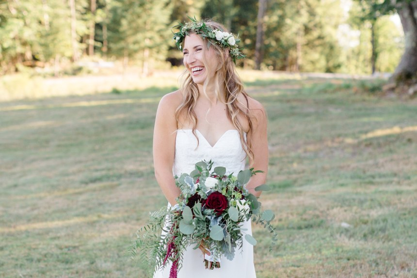 Laughing bride holding bouquet. Hair down with loose waves and floral crown.