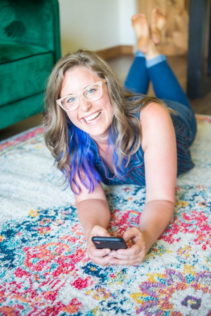 lindsey lockett laying on a colorful rug holding her phone and smiling
