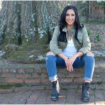 Priya Lahki sitting on a sidewalk wearing jeans and a green jacket