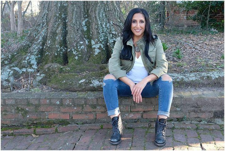 Priya Lahki sitting on a sidewalk wearing jeans and a green jacket