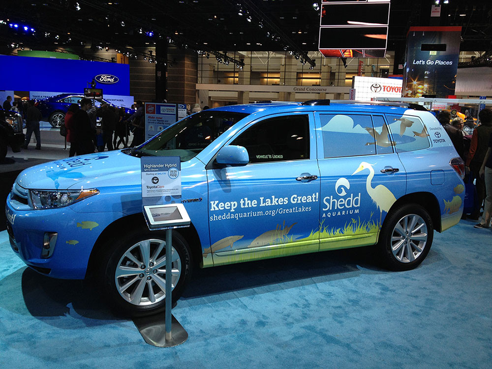 An SUV at the Chicago Auto Show, wrapped bumper to bumper in an illustration of the scenery of the great lakes. A white egret stands near the rear tire, facing the headline, 'Keep the Lakes Great!' and the Shedd Aquarium logo.