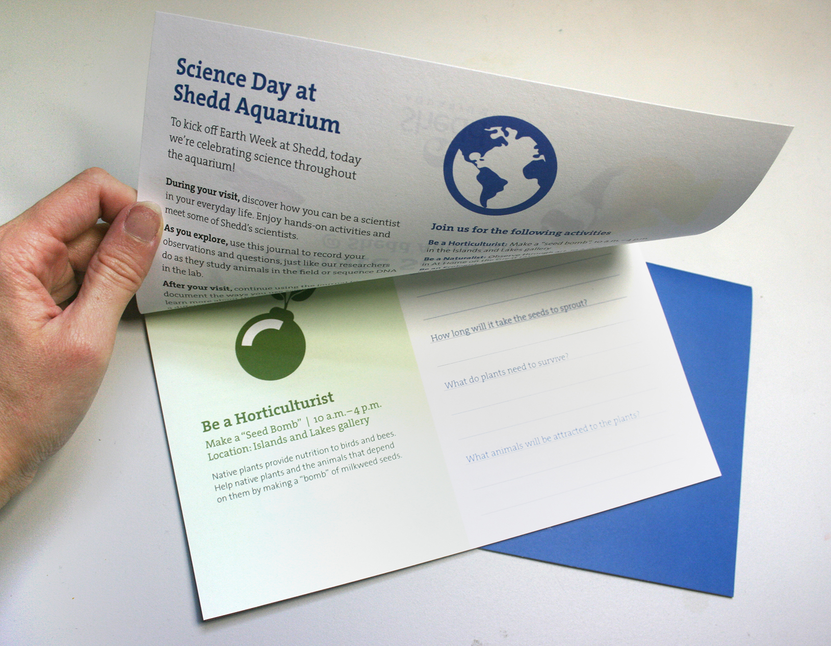 An activity book that opens top-to-bottom. The top page reads 'Science Day at Shedd Aquarium' and contains information about activities available, and the bottom page shows an icon on a green background and information about a specific activity as well as some questions for a participant to answer.