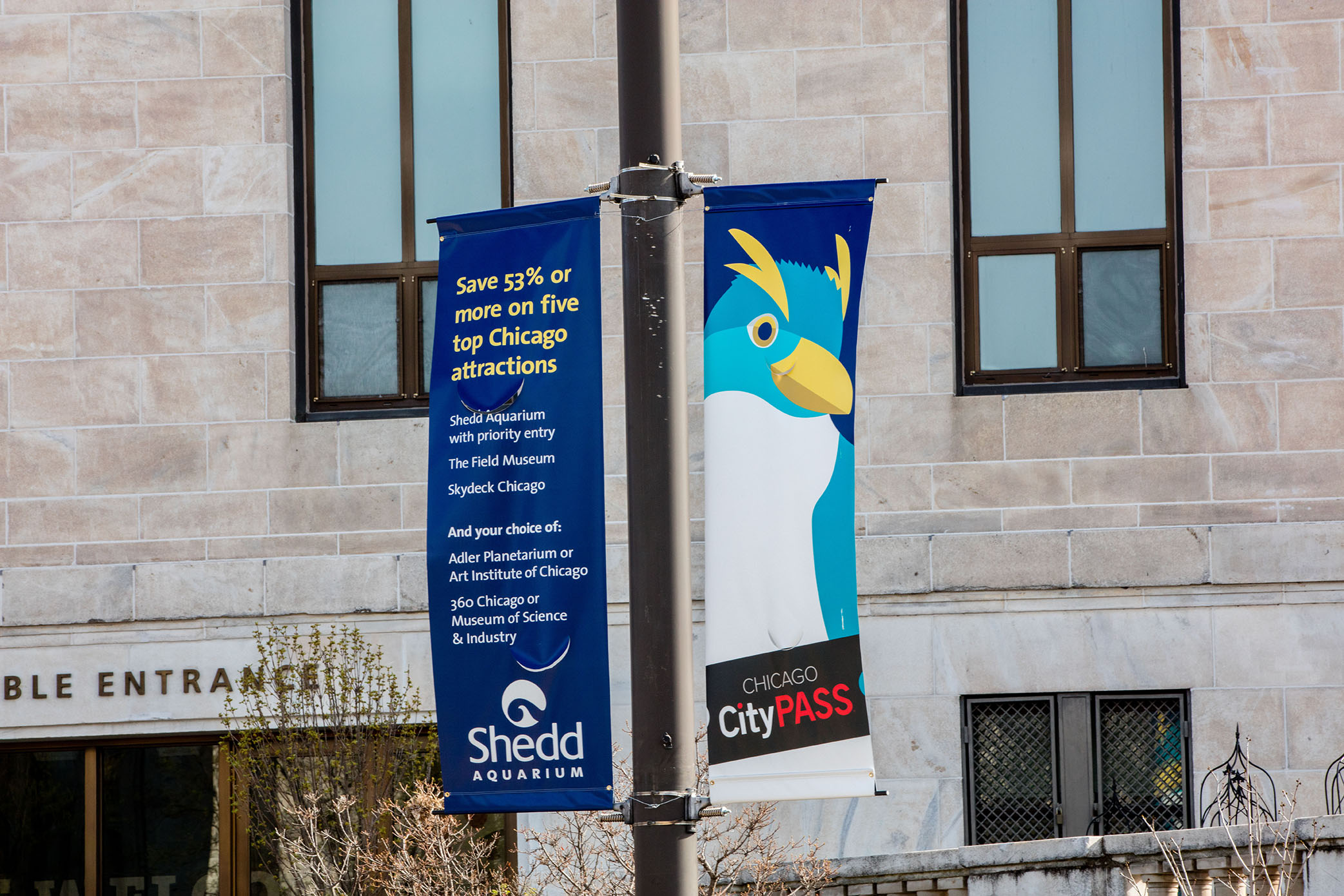 A set of street banners in front of Shedd's accessible entrance, depicting a stylized illustration of a penguin and information about CityPass.