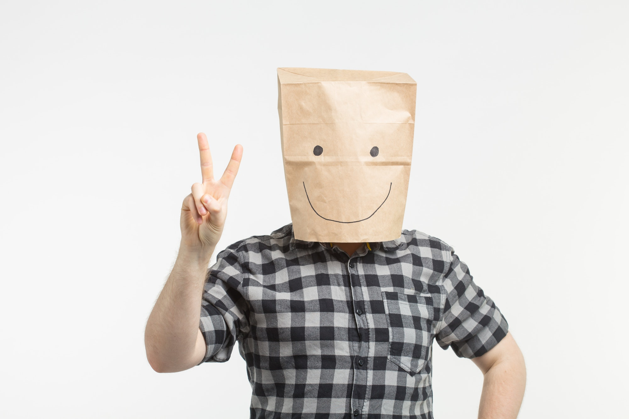 men in paper bag mask showing peace