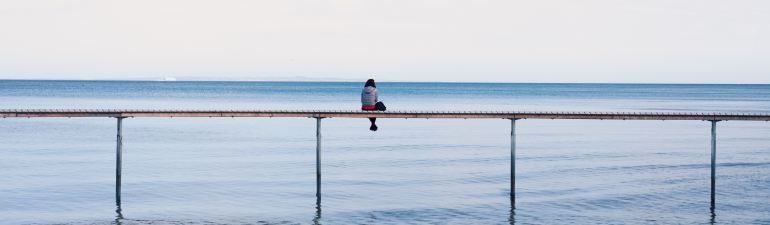 Sitting alone on a dock.