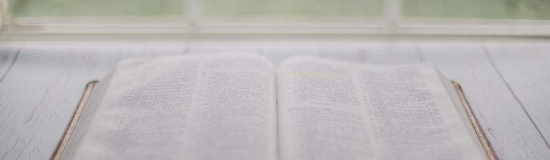 An open Bible on a table in front of a window