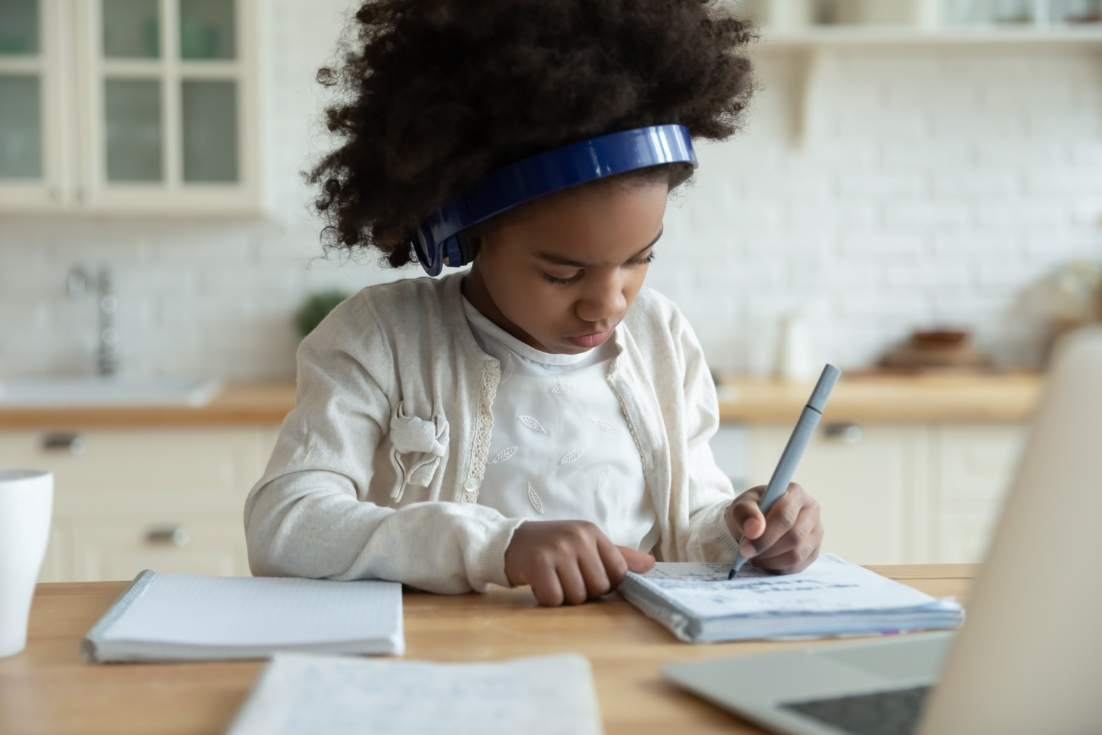 Image of child remote learning with headphones on in front of a laptop, courtesy of Shutterstock.