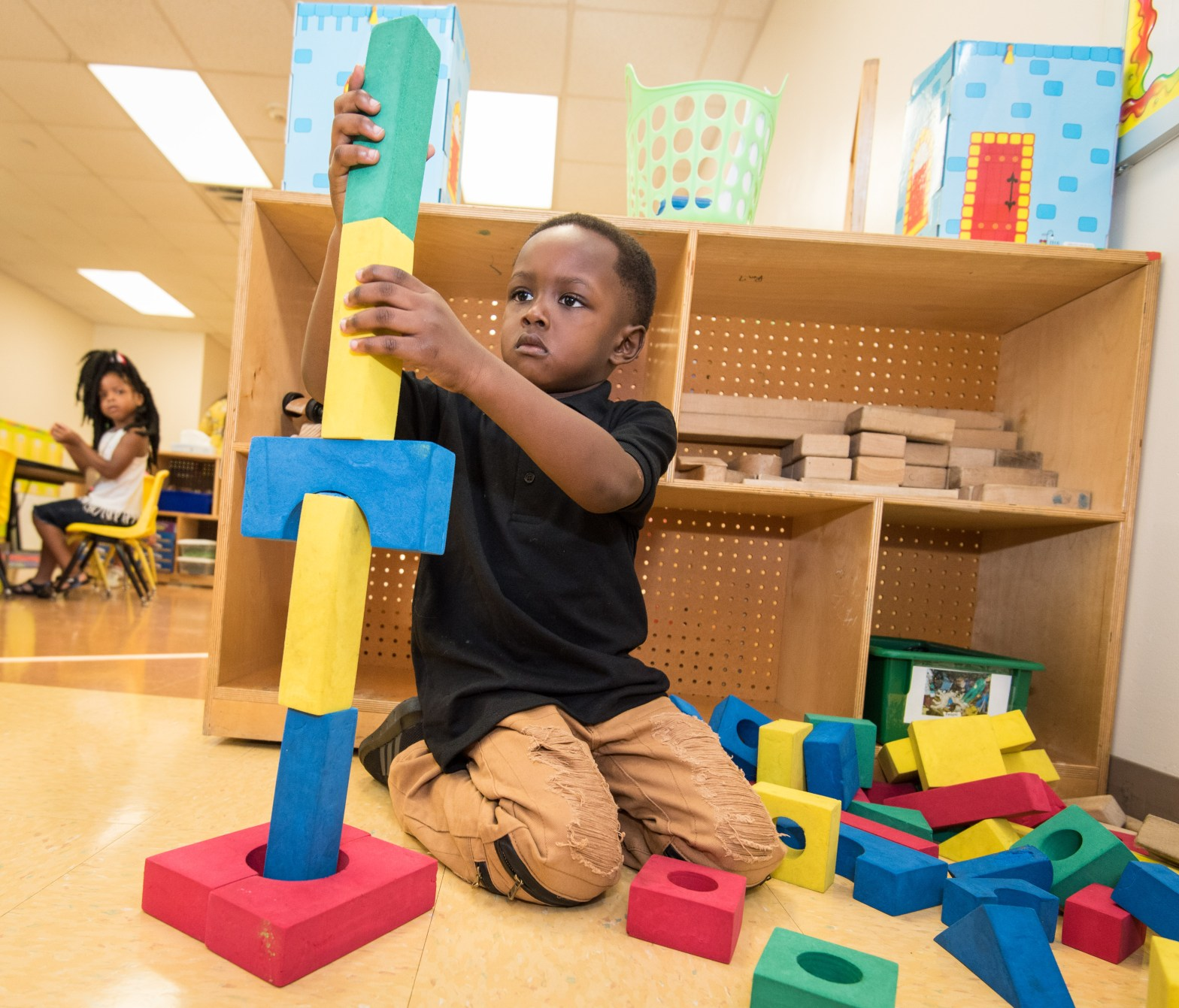 Image of a child building a tower out of blocks; courtesy of HCDE Staff.