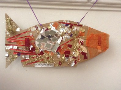 A cardboard cut out fish decorated in tinsel and shiny squares of paper.