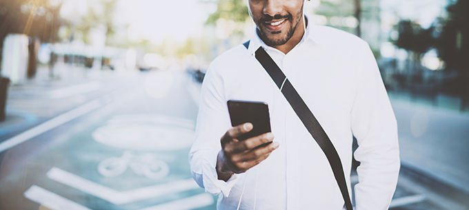 Happy american African man using smartphone outdoor.Portrait of young black cheerful man texting a sms message while listining to music.Blurred background, horizontal wide.Flare effects.