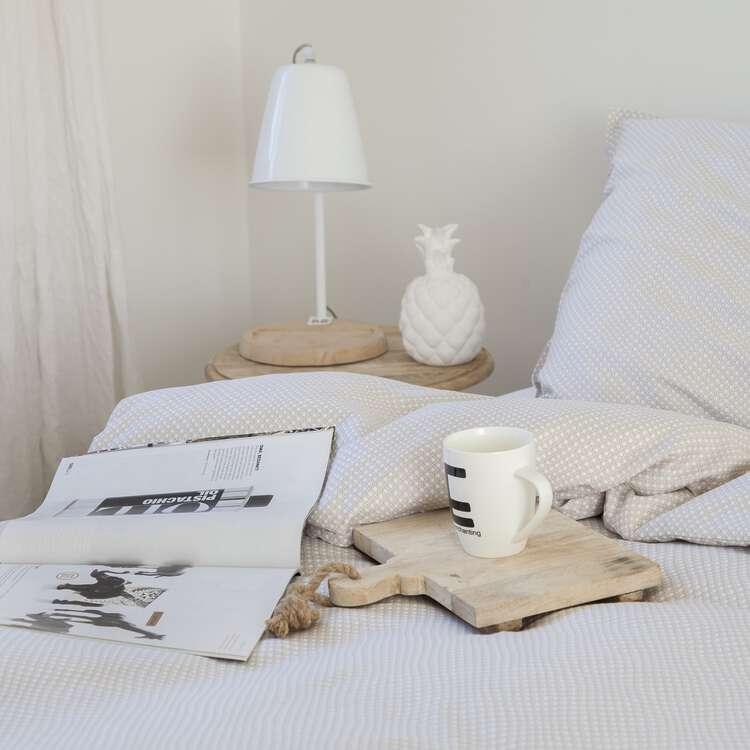 dekbedhoes in beige op een bed met witte muren