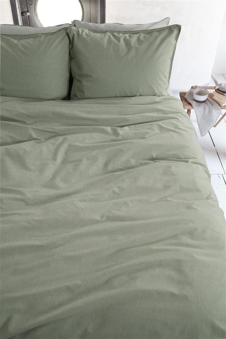 groen dekbedovertrek van katoen op een lichte slaapkamer