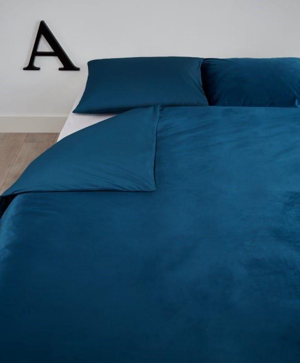 natural slaapkamer met bed opgemaakt in een velvet blauw dekbedovertrek