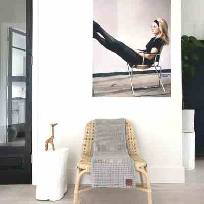 Plaid in de kleur grijs met wafel structuur op een stoel in een natuurlijke kamer.