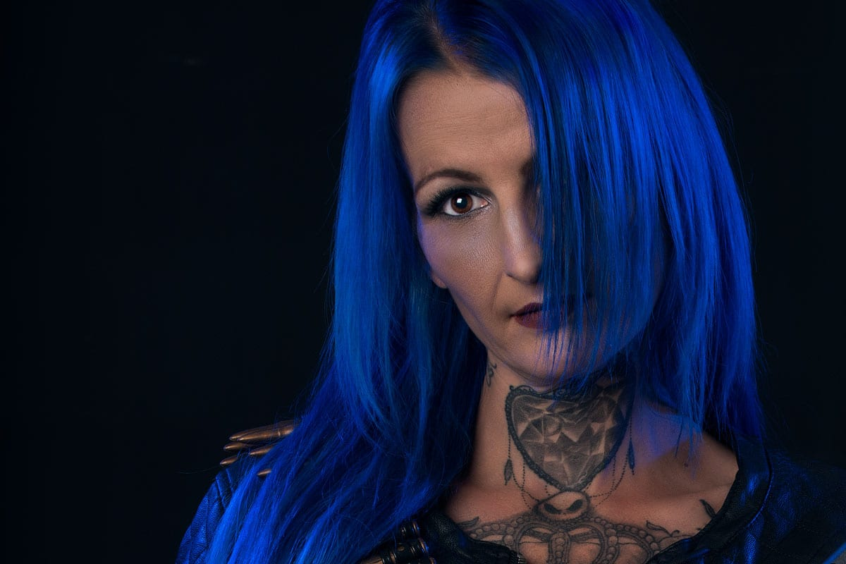portrait of model with blue hair and tattoos